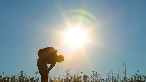 Adult man on summer vacations in countryside. Male silhouette of tired guy hiking. Person walks along grassy hill at sunset sunlight and blue sky background, resting, wiping sweat.
