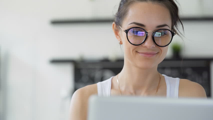 Cute 20s lady working at desk in trendy hipster start up office using shared data. Pretty face close up with emotion of joy and happy success. Student writing a report on successful marketing | Shutterstock HD Video #28705075