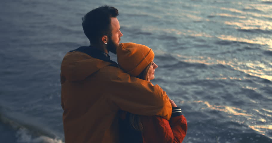 CINEMAGRAPH - seamless loop. Outdoor portrait of young beautiful Caucasian couple enjoying the view of a sunset over the large lake. 4K UHD