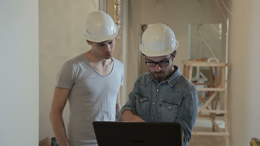 Two builders in helmets are typing a laptop and looking around. People white protective construction caps stand in the middle of the room in which the repair is being carried out. In the process of | Shutterstock HD Video #28715605