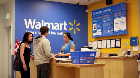 New Westminster, BC, Canada - July 03, 2017 : Motion of people returning goods at customer service counter inside Walmart store with 4k resolution