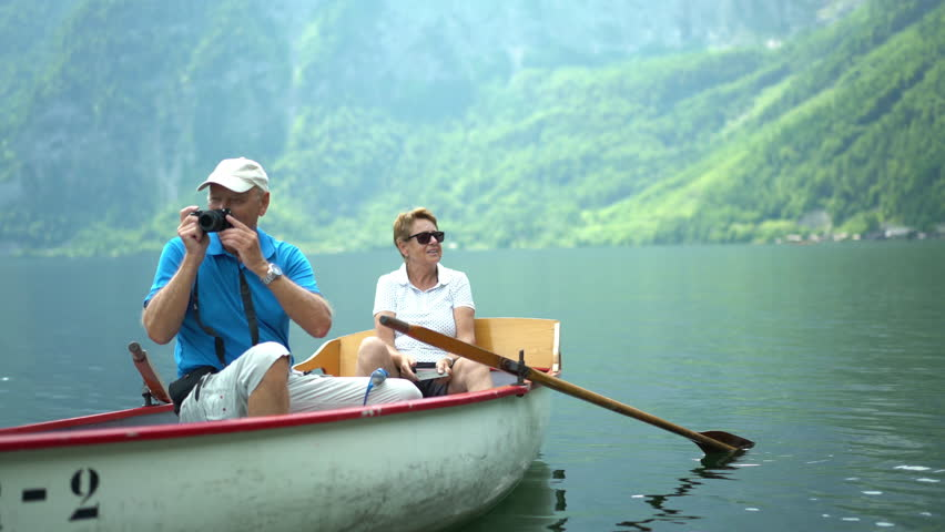 4k travel video, happy active senior tourist couple sitting in rowboat on austrian mountain lake taking souvenir pictures of famous village Hallstatt
