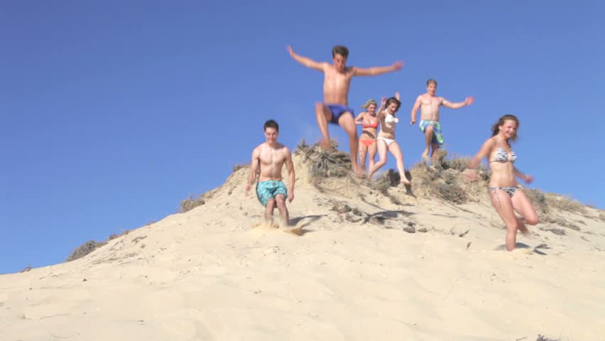 Group of teenage friends appear over peak ofdune before running down and jumping past camera.