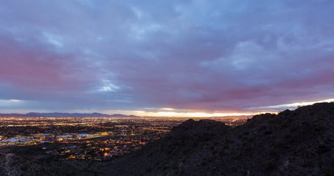 Night time time lapse pan looking over Phoenix, Arizona with heavy clouds and traffic.