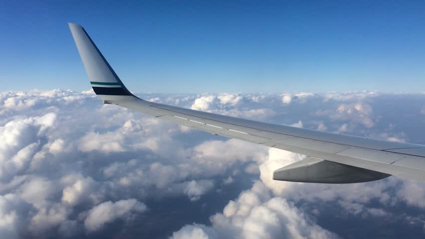 Wing of an airplane flying above the clouds. People look at the sky from the window of the plane, using air transport to travel