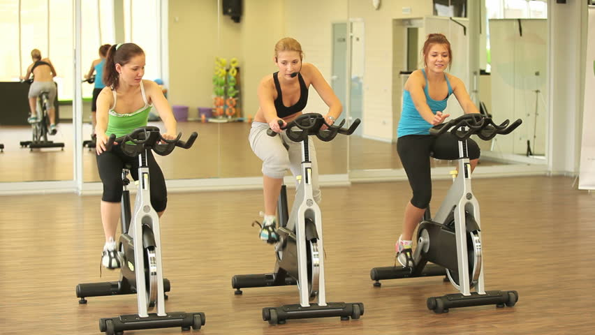 Group of slim girls training on cycles with instructor
