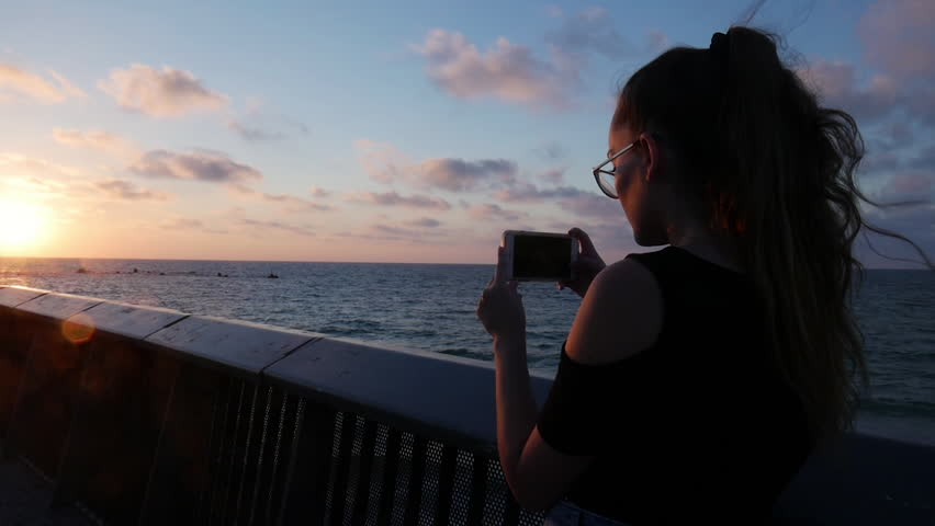 Young girl taking a photo of beautiful sunset over the Mediterranean Sea Jaffa, Tel Aviv.