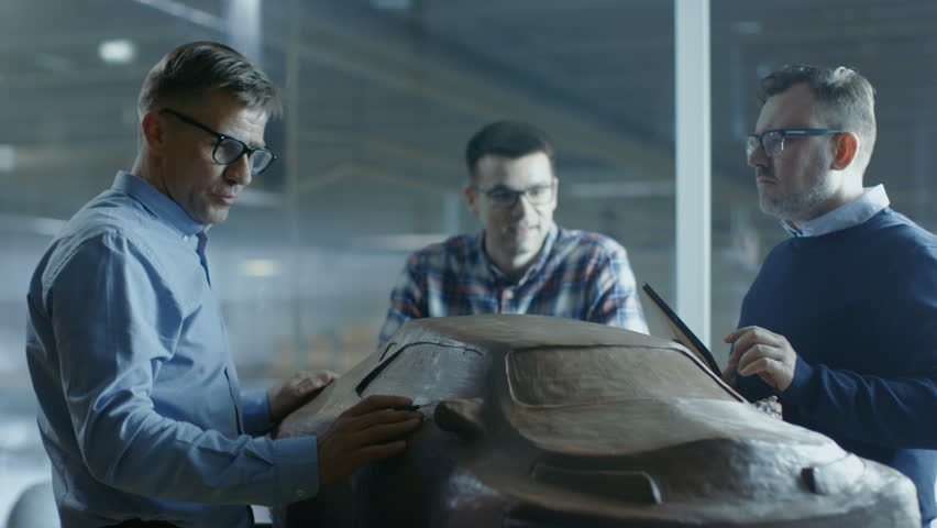 Team of Automotive Design Engineers Discusses New Prototype Design Model Made of Plasticine Clay. They Work in a Large Car Factory. Shot on RED EPIC-W 8K Helium Cinema Camera. | Shutterstock HD Video #28768555