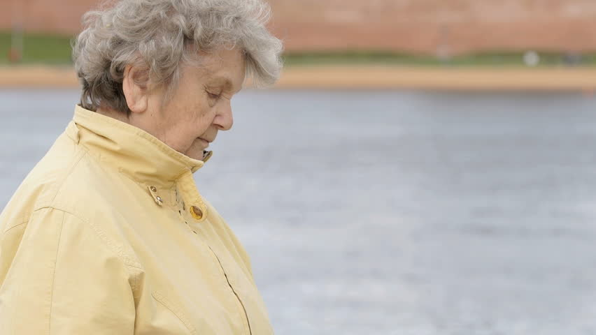 Black wristband. Outdoors a old woman aged 80s dressed in yellow jacket looks at the results of physical activity using a wristband fitness tracker outdoors