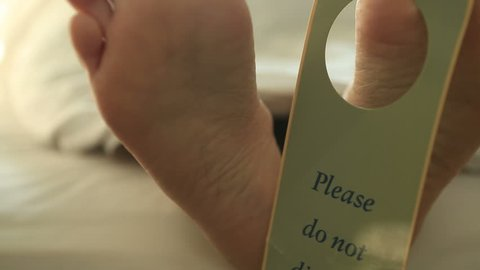 Human's feet on bed with 'do not disturb' sign Happy feet of a person laying down in a comfortable bed in an hotel room with the sign 'do not disturb' hanging on them.