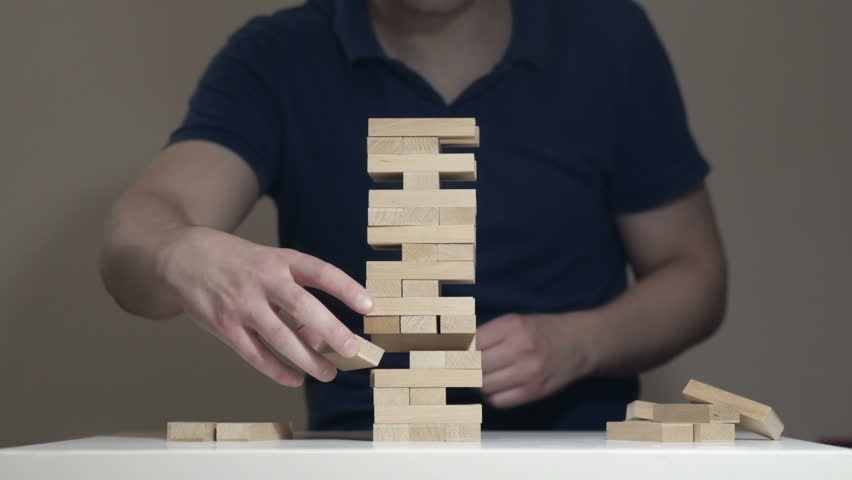 Timelapse loop of assembilng and disassembling Jenga Tower. IT man is playing Jenga game and disassembling the tower. Taking bricks out one by one and putting them back together. Perfect Skills.