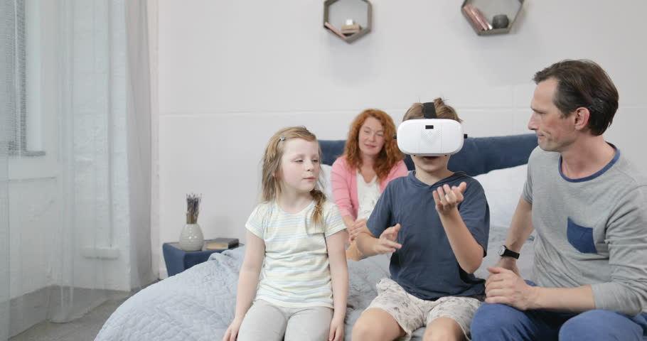 Family Looking At Son Play Games Wearing Virtual Reality Glasses In Bedroom, Parents And Children Spend Morning Together At Home Slow Motion 60   Shutterstock HD Video #28819324