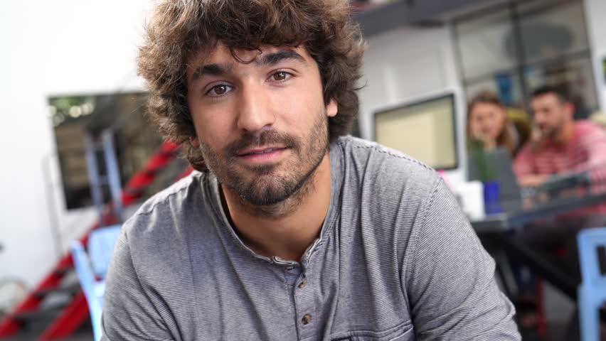 Portrait of cheerful guy sitting in loft office | Shutterstock HD Video #28822045