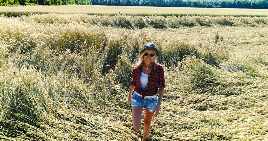 Sexy woman with hat and short jeans and sunglasses goes through rye field in summer | Shutterstock HD Video #28825405