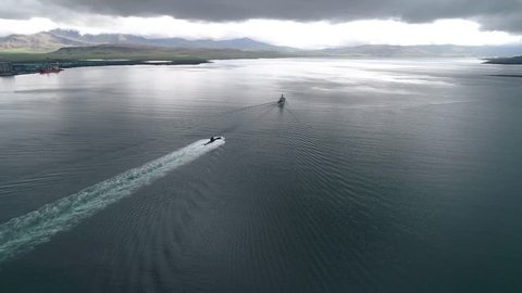 warships sailing into Icelandic fjord, a coast guard ship followed by a submarine