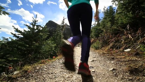 Young sportive woman trail running in nature. Female running on mountain trail. Cross country