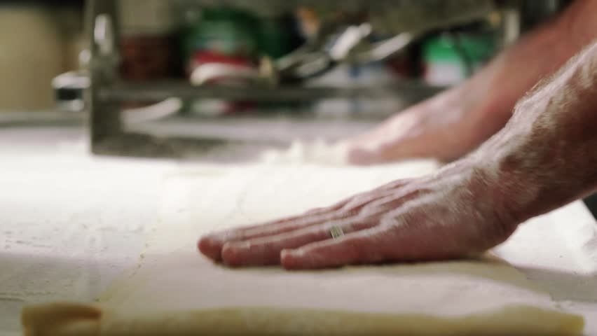 Chef prepares dough for making pasta, flouring the dough and kneading it.