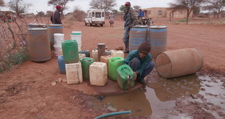 People collecting water in containers from a communial tap due to severe drought in South Africa