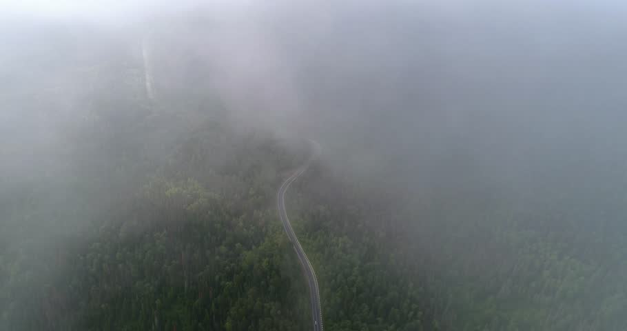 Flight in the clouds. A view of the earth through the clouds. A winding mountain road. The road is on the heights of the forest hills. Aerial View. | Shutterstock HD Video #28860955