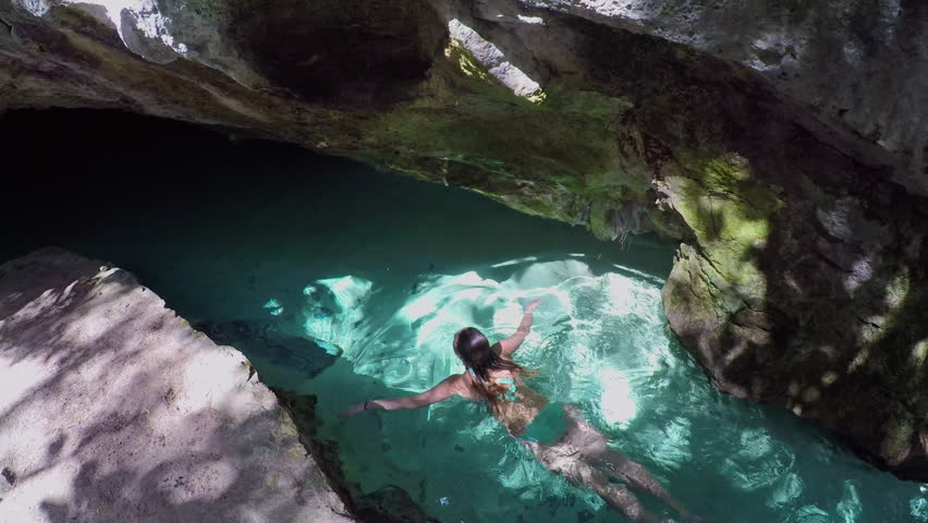 CLOSE UP Beautiful young woman in bikini swimming in stunning crystal clear river through the rocky passage into the famous Grand Cenote cave, Mexico. Female bathing in groundwater on sunny summer day