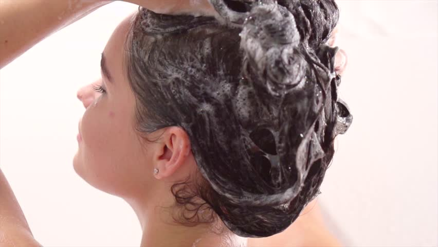 Beauty young woman washing her hair with shampoo. Beautiful brunette model girl takes shower, washing hair in a bath. Hair care, beauty and wellbeing concept. Slow motion 240 fps. 4K UHD video.