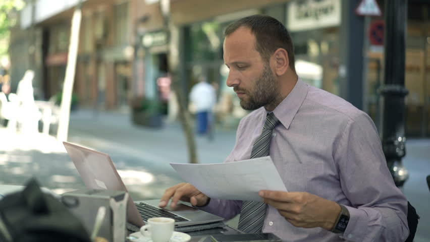 Young businessman working with documents and laptop sitting in cafe  - 4K stock video clip