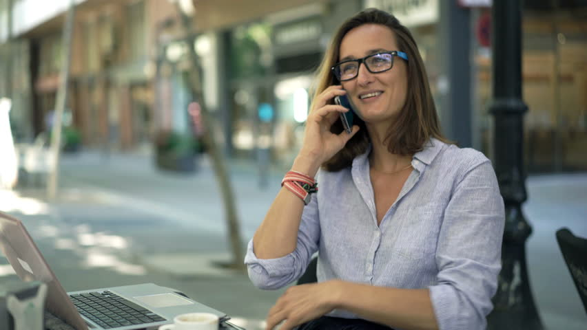 Young businesswoman drinking coffee and talking on cellphone sitting in cafe  | Shutterstock HD Video #28874725