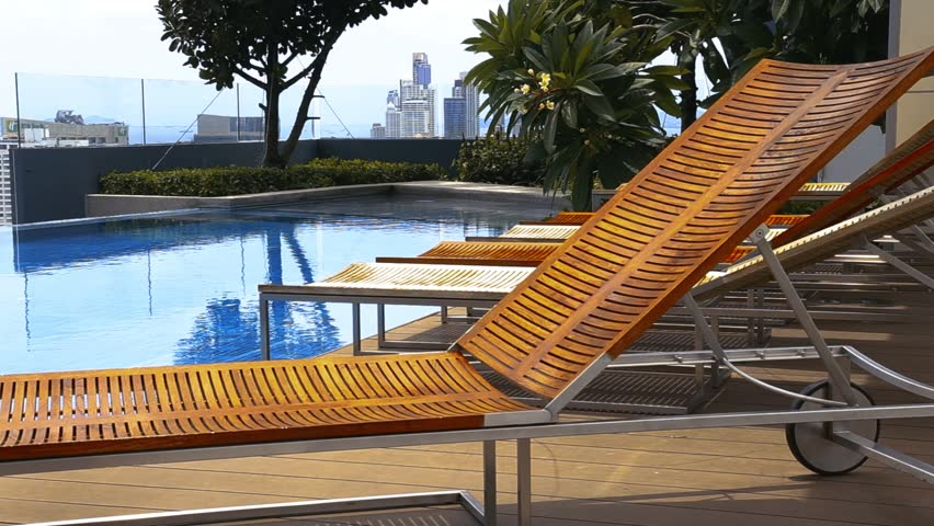 wooden teak Lounge Chairs, Patio Furniture, at Poolside with garden background