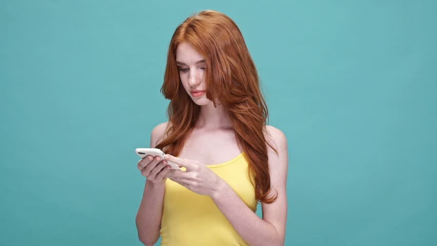 Smiling redheaded girl holding mobile phone and texting while standing isolated over blue background | Shutterstock HD Video #28892755