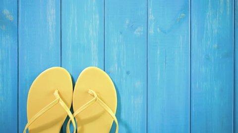 Bright women's flip flops on a wood board.