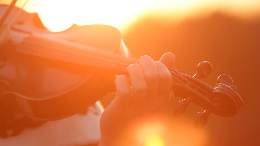 Playing fiddle outdoors at sunset