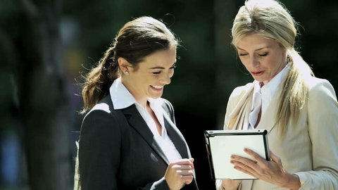 Young Caucasian career women meeting outside in city to share business success on tablet computer RED EPIC