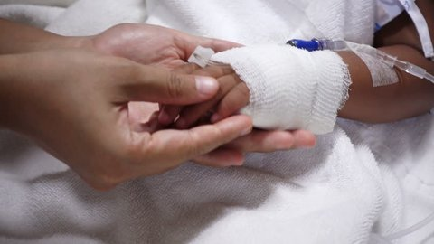 Close up of young parent and sick little daughter holding bandaged hands for comfort in a hospital bed