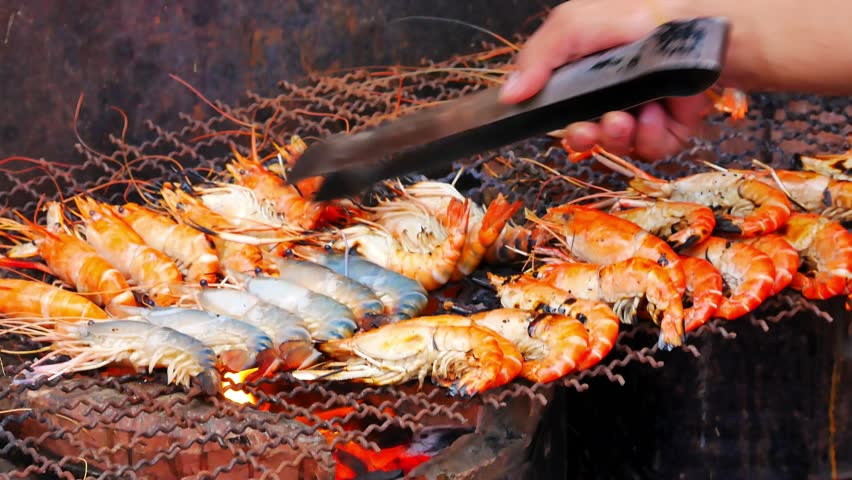 Grilling shrimps on barbecue. Hand puts the shrimp on grill. Grilled seafood on bbq. grilled shrimps at street food festival. Cooking seafood on grill at china town ,Yaowarat , Bangkok , Thailand