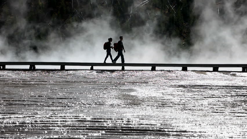 YELLOWSTONE NATIONAL PARK, WYOMING CIRCA 2009:  One of Americas most visited destinations. Young man and woman walking on a boardwalk. Dark silhouette against bright water and steam.