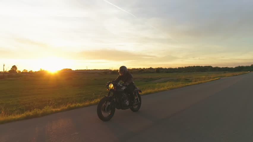Riding vintage custom made cafe racer on a sunset