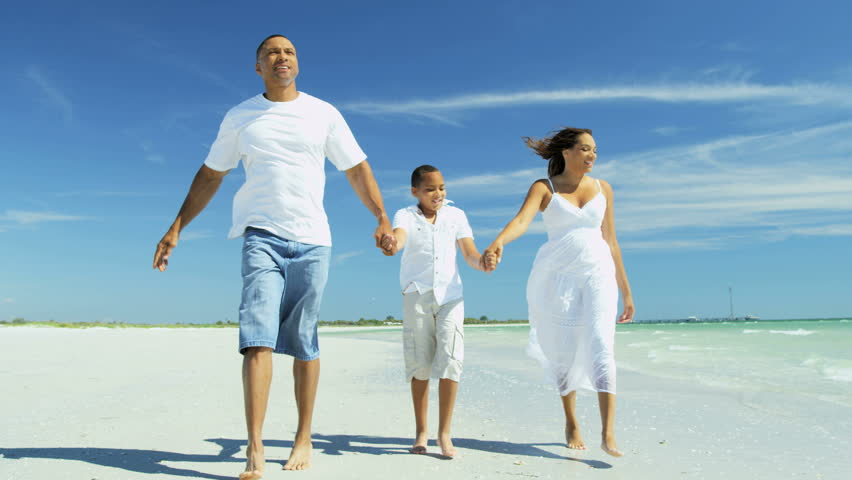 Happy ethnic family wearing white clothing holding hands and relaxing on beach holiday RED EPIC | Shutterstock HD Video #28979671