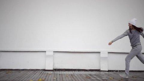 Beautiful teenage girl dancing on the street.