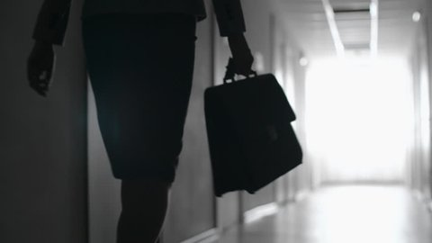 Tracking with mid-section of silhouette of businesswoman with briefcase walking along hallway towards bright light