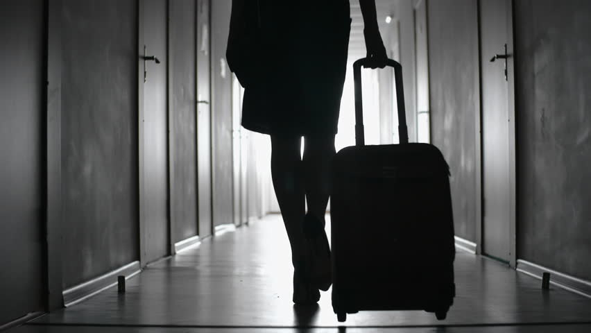 Tracking with low-section of silhouette of elegant woman in skirt and high heels shoes carrying suitcase and walking along hallway of hotel towards her room; black and white slow motion shot | Shutterstock HD Video #28997305