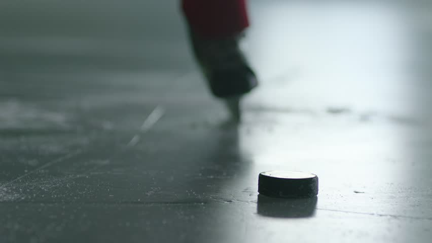 close up of ice hockey player taking a slap shot with hockey stick in slow motion