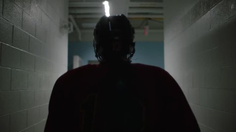 dramatic silhouette ice hockey player walking from change room in slow motion towards arena rink arena