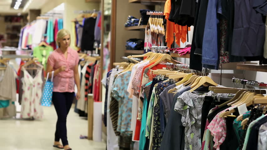 Woman looking at clothes on rail in clothing store