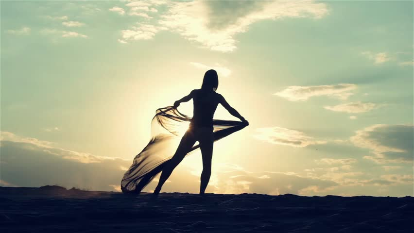 Silhouette of a dancing woman at sunset