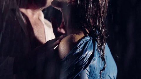 close-up. male hand stroking the naked woman's shoulder. love the rain at night. love story couple