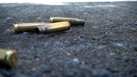 Empty bullet cases fall in slow motion in street