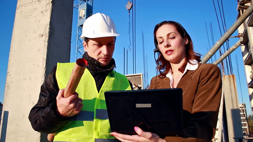 Team work on construction projects ; female and men are constructors considered building plan on a laptop,video clip