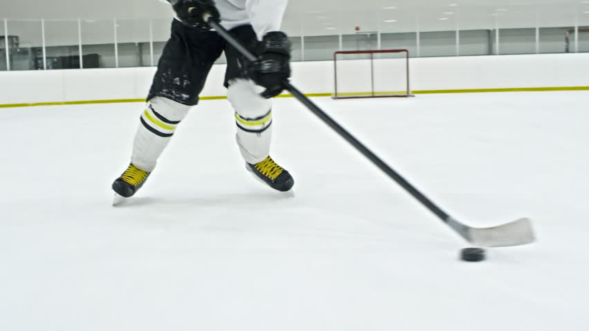 Tracking low-section shot of unrecognizable hockey player in white uniform dribbling puck in ice rink during practice