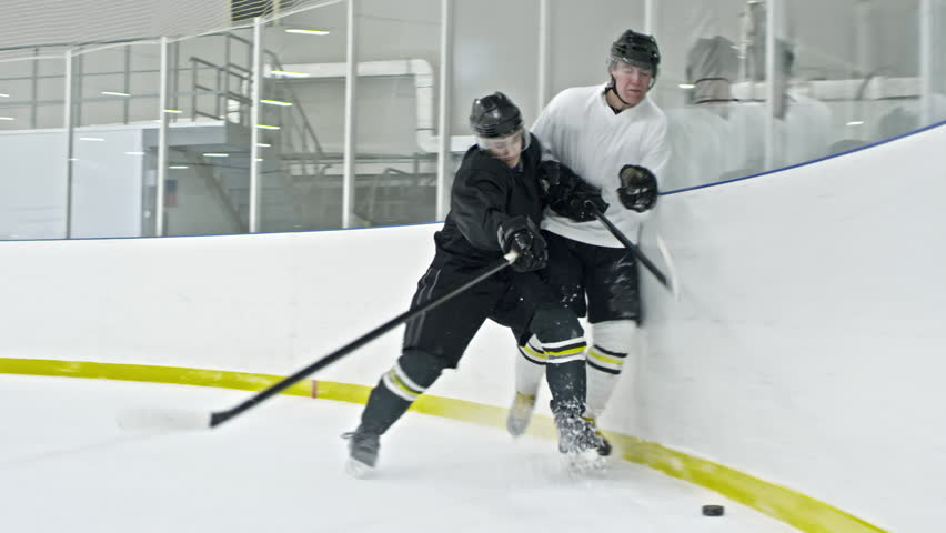 Slow motion tracking of hockey forward in white uniform dribbling puck along ice rink board, then falling as player from opposing team boarding him
