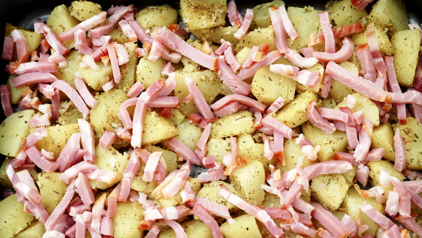 Peeled potatoes with spices, becon meat and onion slices ready to be roasted close up. Food background. Rack focus